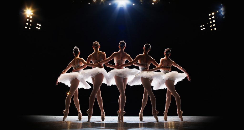 A group of talented dancers stand in the spotlight